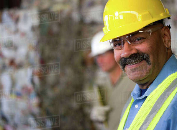 Portrait of mature male worker in hard hat, in front of stacked rubbish at recycling plant Royalty-free stock photo