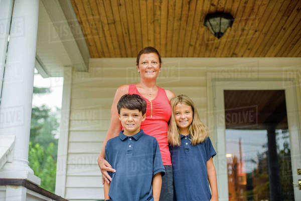 Portrait of male and female  elementary school twins with mother outside home porch Royalty-free stock photo
