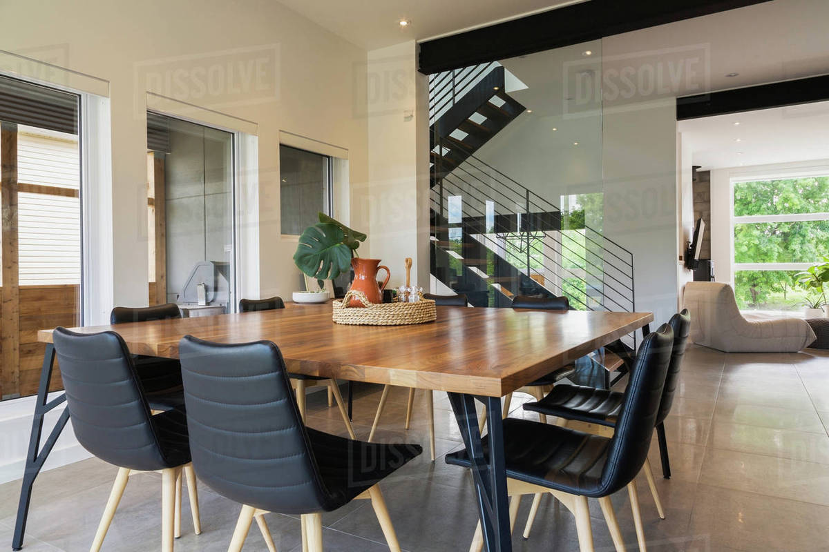 American Walnut Wood Dining Table And Black Leather Sitting Chairs With Ash Wood Legs In The Dining Room Inside A Modern Cube Style Home Quebec Canada Stock Photo Dissolve