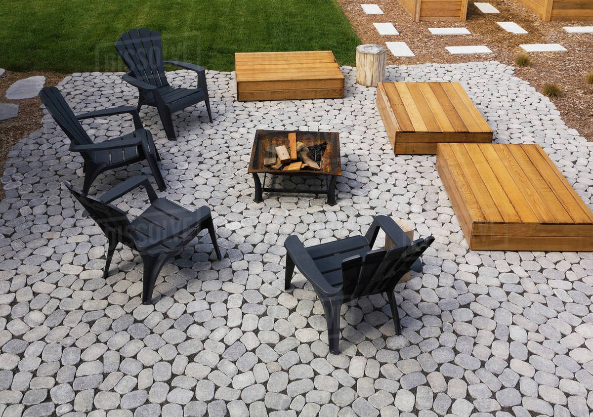 Grey Paving Stone Patio With Black Adirondack Sitting Chairs Slightly Raised Flat Rectangular Red Cedar Wooden Bench Platforms Around A Metal Firepit In