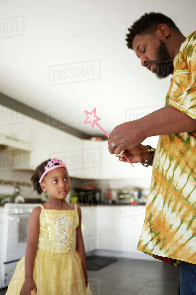 Mature man repairing fairy wand for daughter in kitchen Royalty-free stock photo