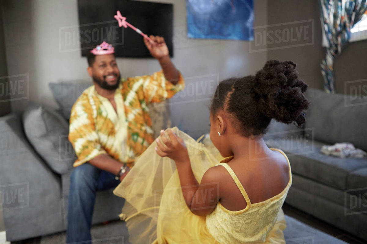 Man casting spell on daughter in fairy costume in living room Royalty-free stock photo