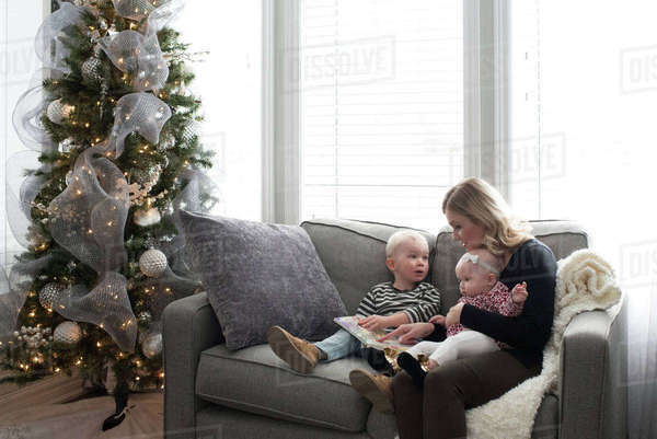 Mother and children sitting on sofa, looking at book Royalty-free stock photo