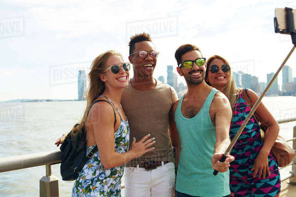 Four adult friends taking smartphone selfie on waterfront with skyline, New York, USA Royalty-free stock photo