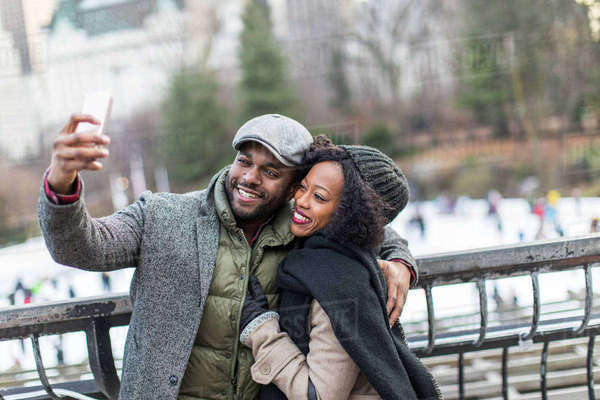Couple taking smartphone selfie on city balcony Royalty-free stock photo