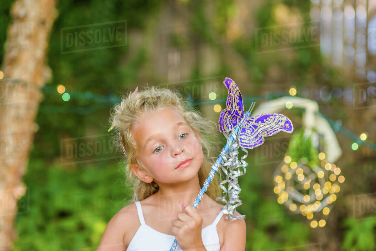 Portrait of young girl holding butterfly wand Royalty-free stock photo