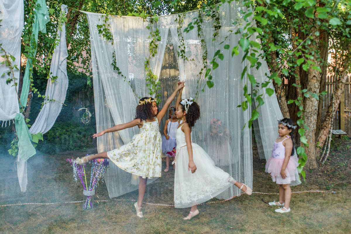 Two young girls, dressed as fairies, dancing outdoors, younger girl watching from side Royalty-free stock photo