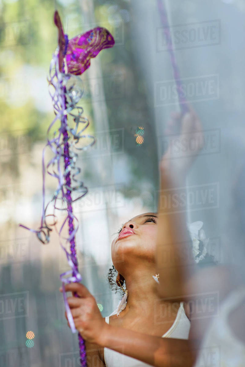 Young girl dressed as fairy, holding wand, playing outdoors Royalty-free stock photo