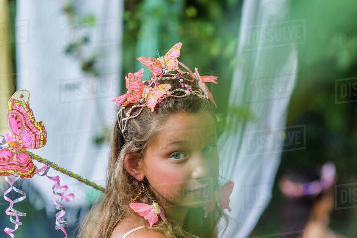 Portrait of young girl wearing butterflies in hair, holding wand Royalty-free stock photo