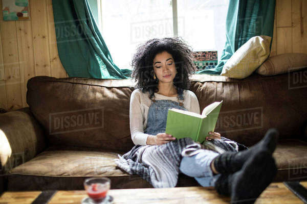 Young woman sitting on sofa, reading book Royalty-free stock photo