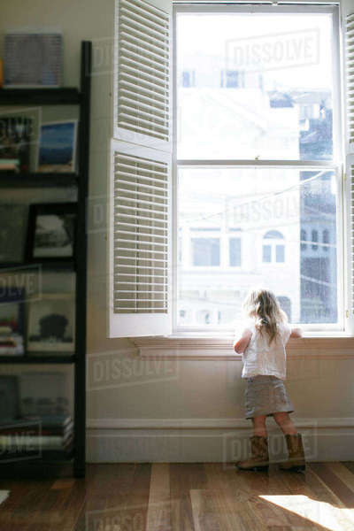 Rear view of female toddler looking through apartment window Royalty-free stock photo