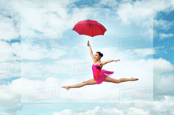 Ballerina with umbrella, leaping against cloudy sky Royalty-free stock photo
