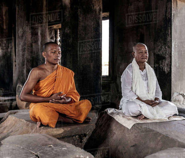 Senior and young monk meditating in temple in Angkor Wat, Siem Reap, Cambodia Royalty-free stock photo