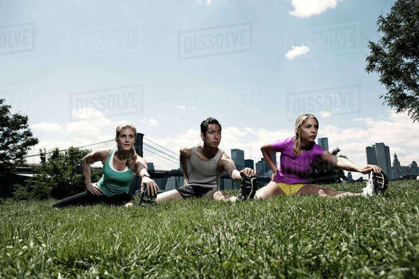 Three people stretching in park Royalty-free stock photo