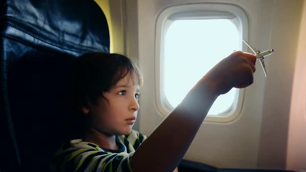 Boy (6-7) in airplane playing with toy plane Royalty-free stock video