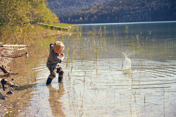 Boy skimming stones in lake, Kochel, Bavaria, Germany Royalty-free stock photo