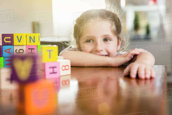 Girl playing with alphabet bricks at kitchen table Royalty-free stock photo