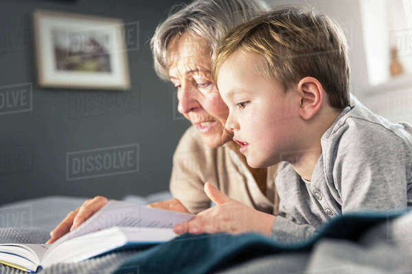 Senior woman reading storybook to grandson on bed Royalty-free stock photo