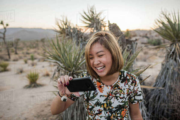 Young woman taking smartphone selfie in Joshua Tree National Park at dusk, California, USA Royalty-free stock photo
