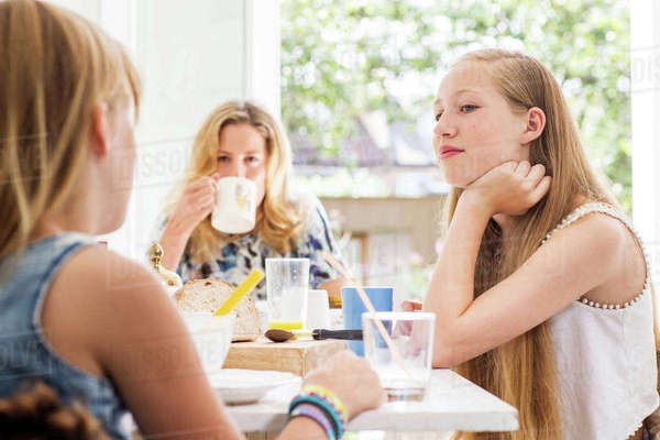 Portrait of mother and daughters in kitchen having breakfast together Royalty-free stock photo