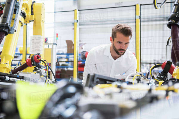 Young male engineer inspecting machinery in engineering factory Royalty-free stock photo