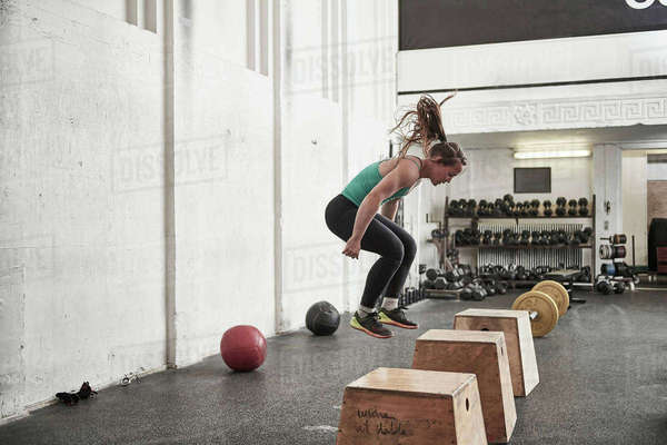 Woman jumping onto fitness box in cross training gym Royalty-free stock photo