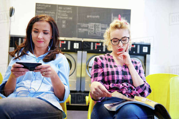 Two women sitting in laundrette reading magazine and looking at smartphone Royalty-free stock photo