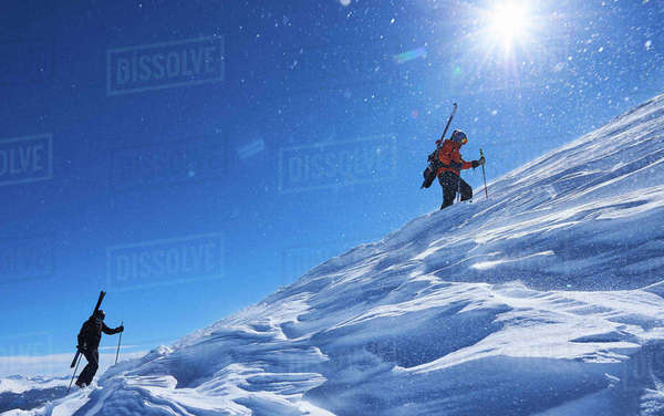 Two male skiers trudging up snow covered mountain, Aspen, Colorado, USA Royalty-free stock photo