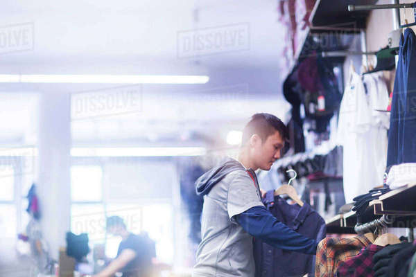 Young male skateboarder looking at shirt in skateboard shop Royalty-free stock photo