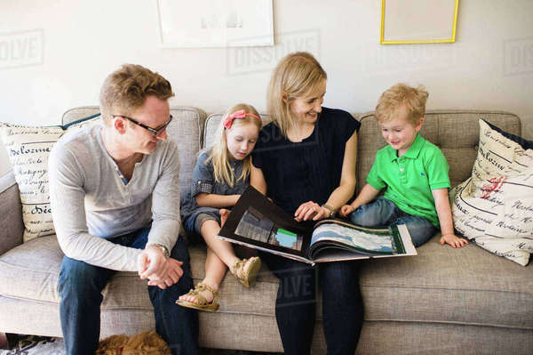 Parents on sofa reading storybook to son and daughter Royalty-free stock photo