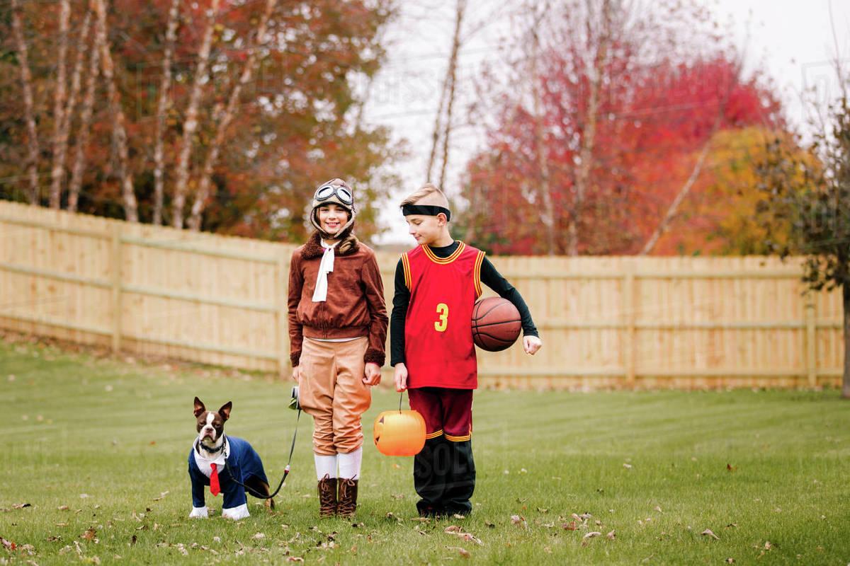 portrait of boy, twin sister and boston terrier wearing halloween