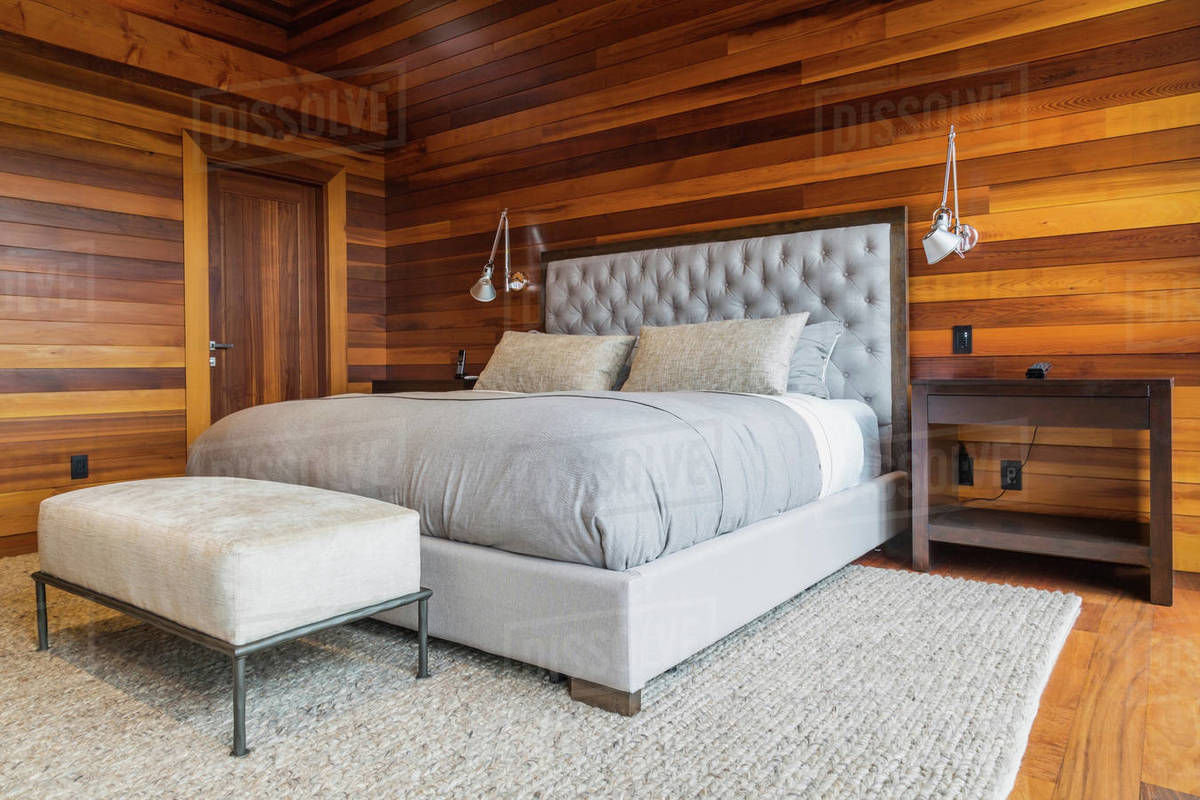 King size bed in master bedroom inside luxurious cedar wood home stock photo