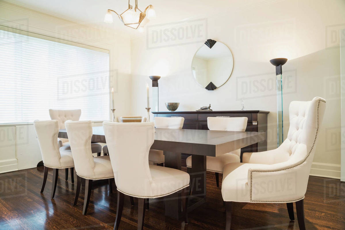 Dark Wood Dining Table With White Cloth Upholstered Chairs In Dining Room Dark Stained Wood Flooring Stock Photo Dissolve