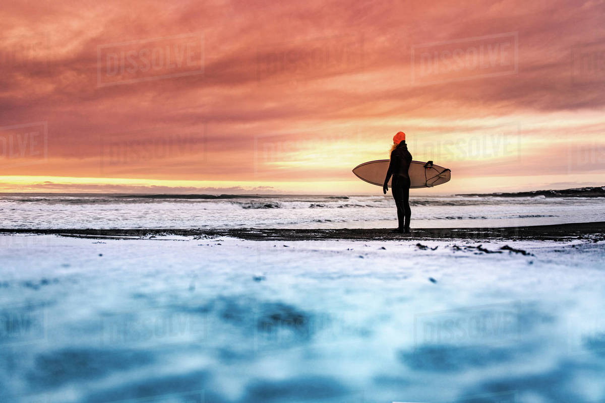 Rear view of  a woman standing on a beach holding a surfboard, looking out to sea with a sunset in the background. Royalty-free stock photo