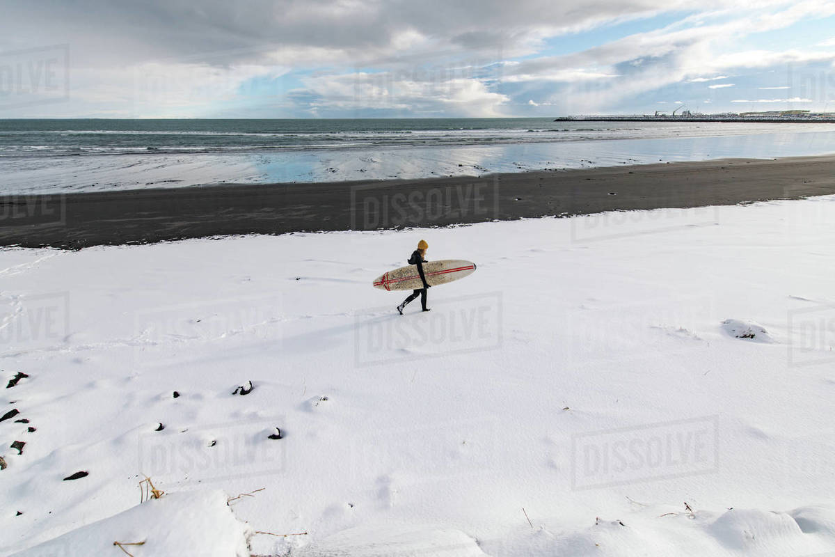 Woman wearing a wetsuit and holding a surfboard walking along a snowy beach. Royalty-free stock photo