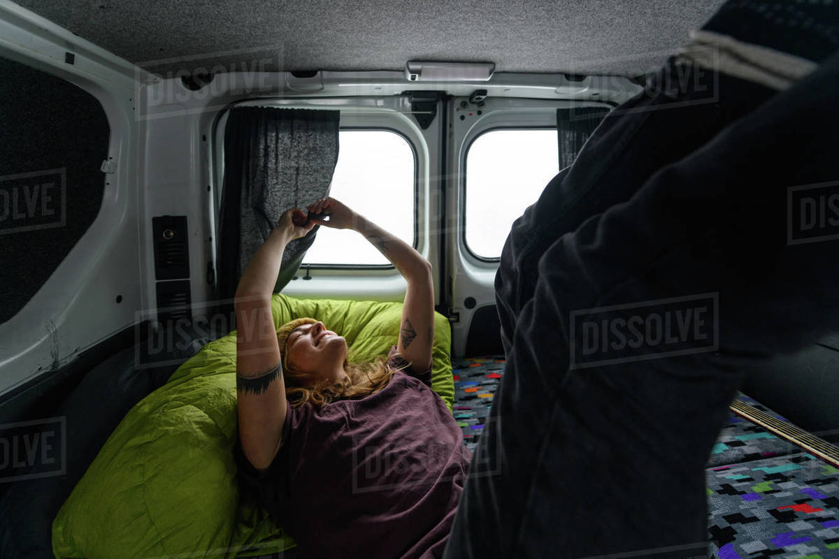 A woman lying on a mattress in a campervan with arms raised. Winter road trip Royalty-free stock photo