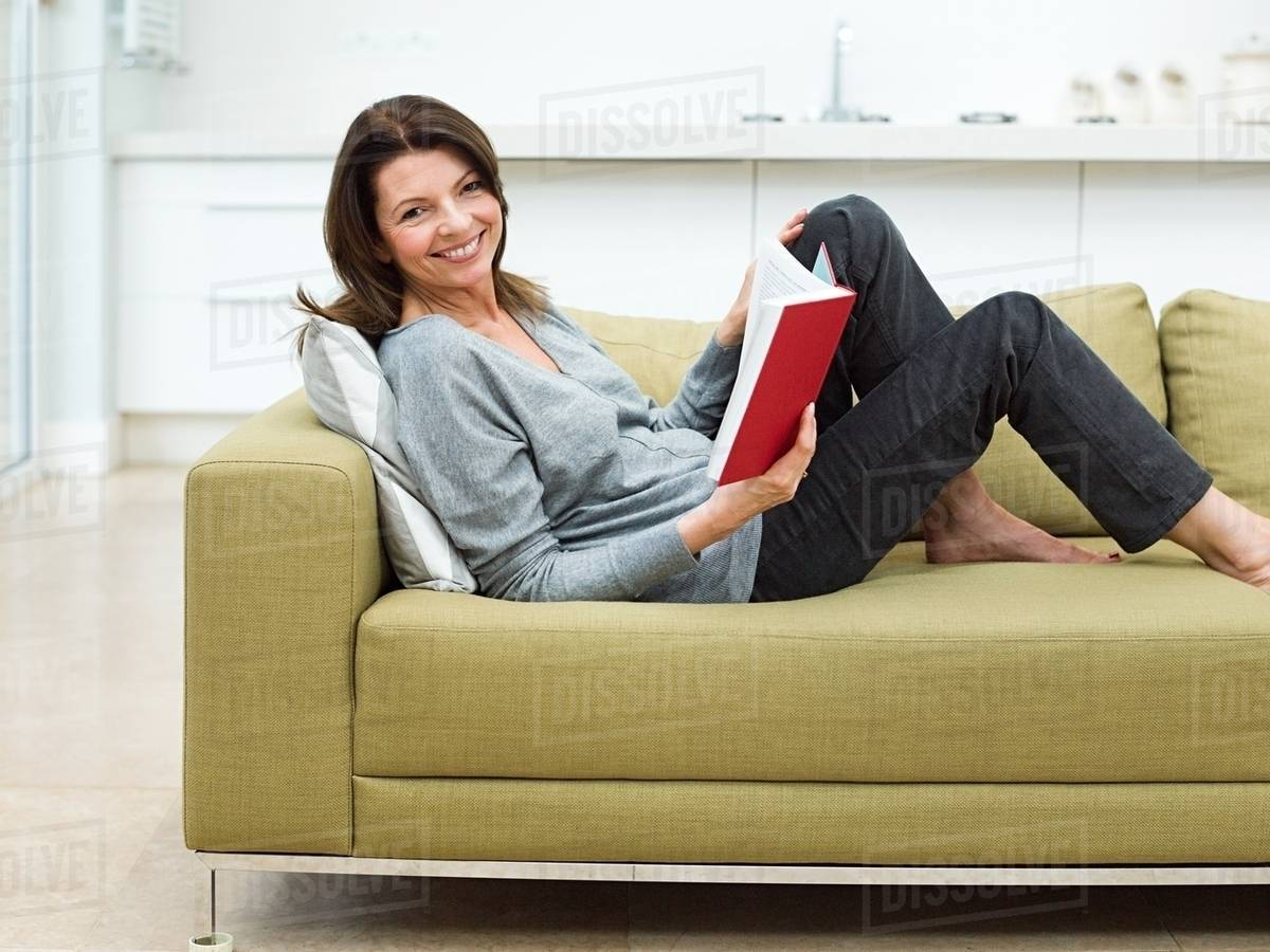 Woman Sitting On Sofa Reading Book