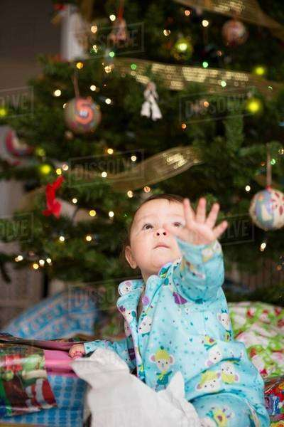 Baby girl reaching up, christmas tree in background Royalty-free stock photo