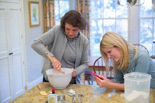 Senior woman and granddaughter baking and using cellphone Royalty-free stock photo