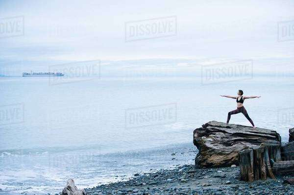 Mature woman practicing yoga pose whilst standing on large driftwood tree stump on beach Royalty-free stock photo