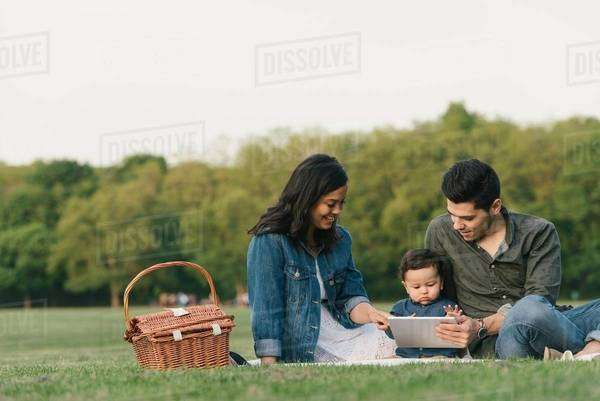 Mother, father and baby boy sitting outdoors using digital tablet Royalty-free stock photo