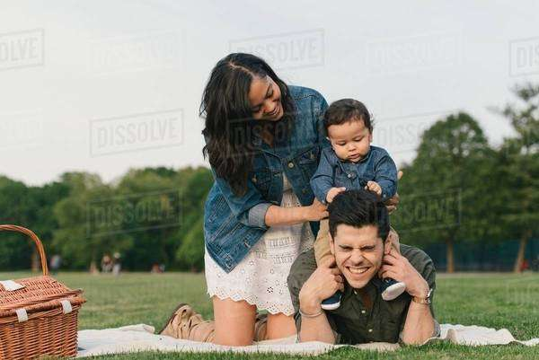 Mother steadying baby boy sitting on fathers shoulders, pulling hair Royalty-free stock photo