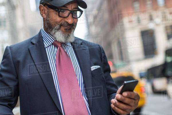 Mature businessman using smartphone on street Royalty-free stock photo