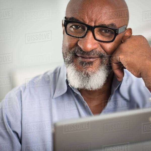 Portrait of mature man with greying beard and glasses, looking at camera smiling Royalty-free stock photo
