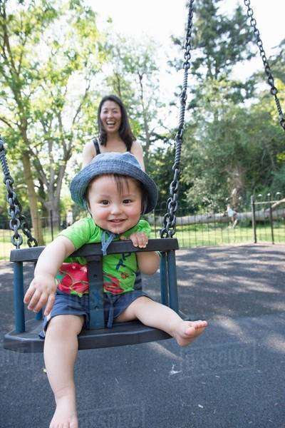 Portrait of baby boy with mother playing on park swing Royalty-free stock photo