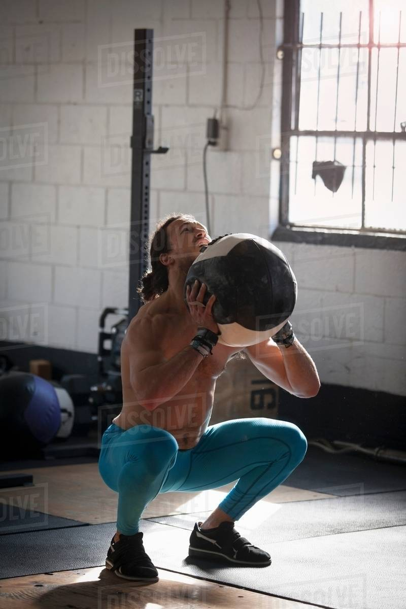 Man doing squats with medicine ball in gym stock photo