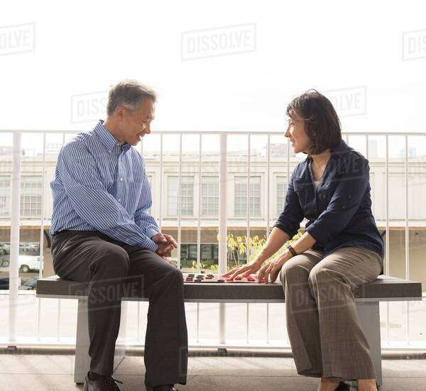 Mature couple sitting on bench face to face playing draughts Royalty-free stock photo