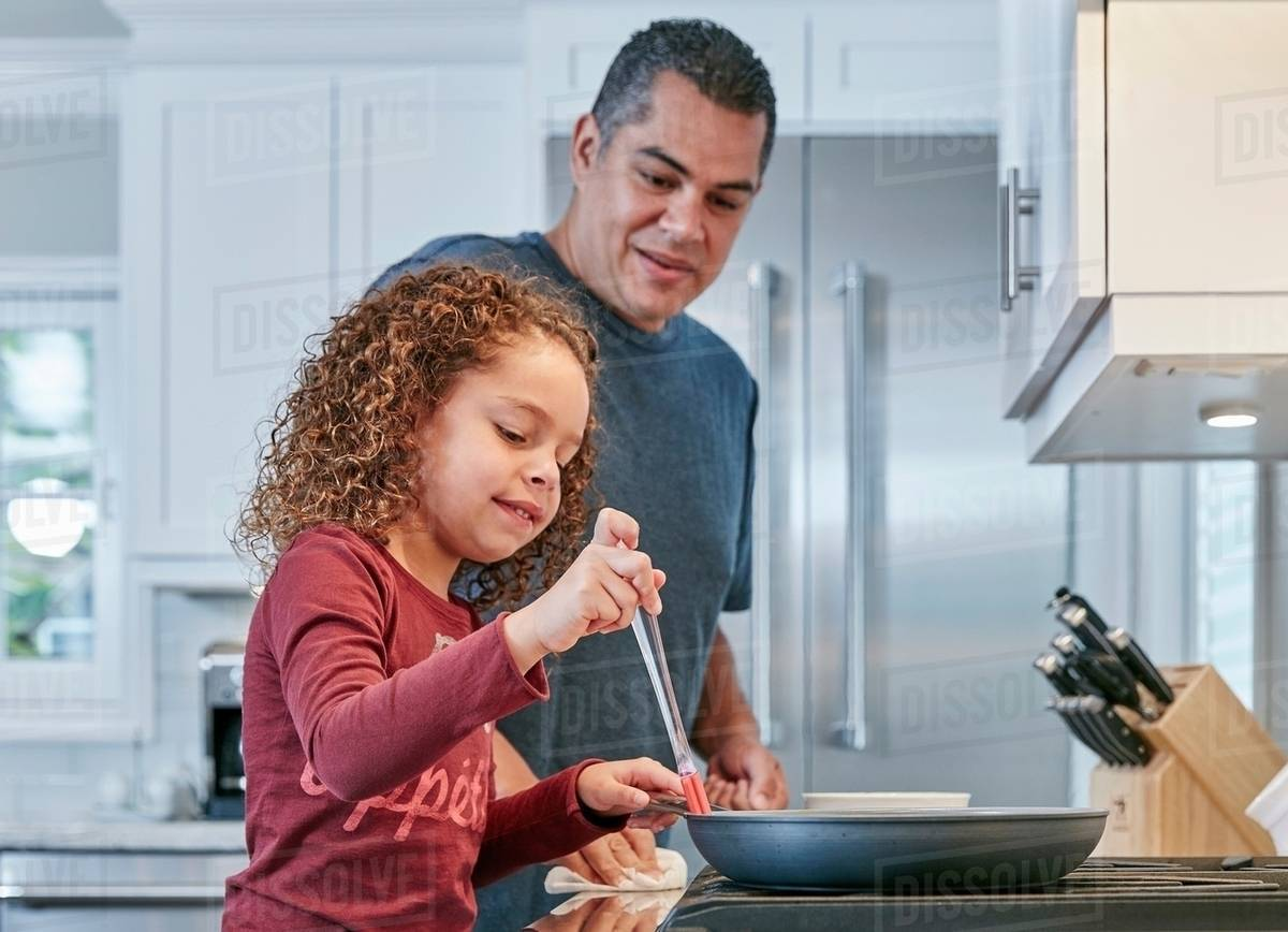 Father helping daughter cook on hob in kitchen - Stock Photo - Dissolve