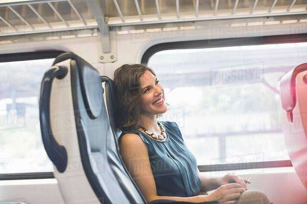 Mid adult woman on train, smiling Royalty-free stock photo