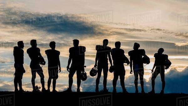 Silhouette of group of young american football players, standing in row Royalty-free stock photo